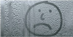 sad face drawn on window with bad condensation