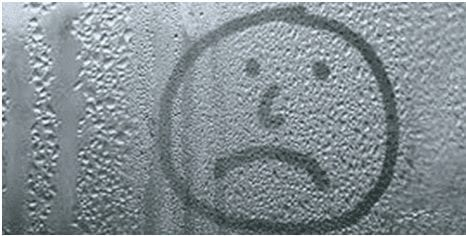 Unhappy face drawn on a window with bad condensation