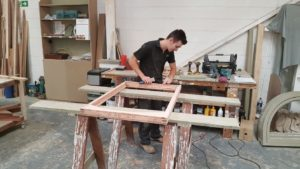Joinery apprentice working hard on wood window frame for his award