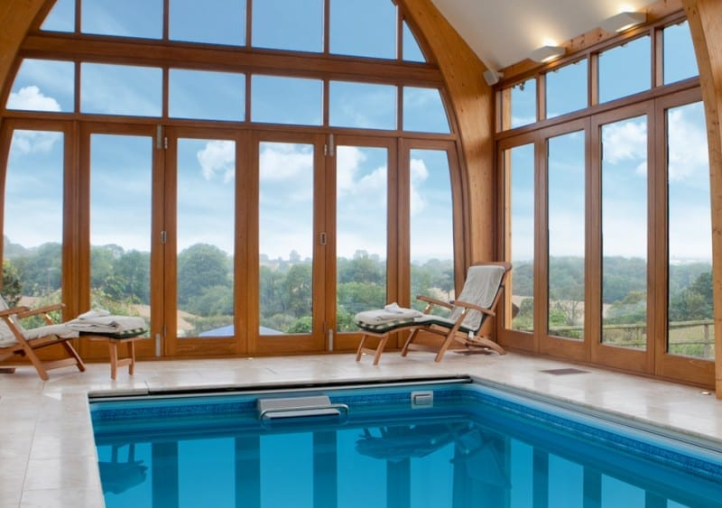 gallery pool with massive arched wooden windows and lift and slide patio doors