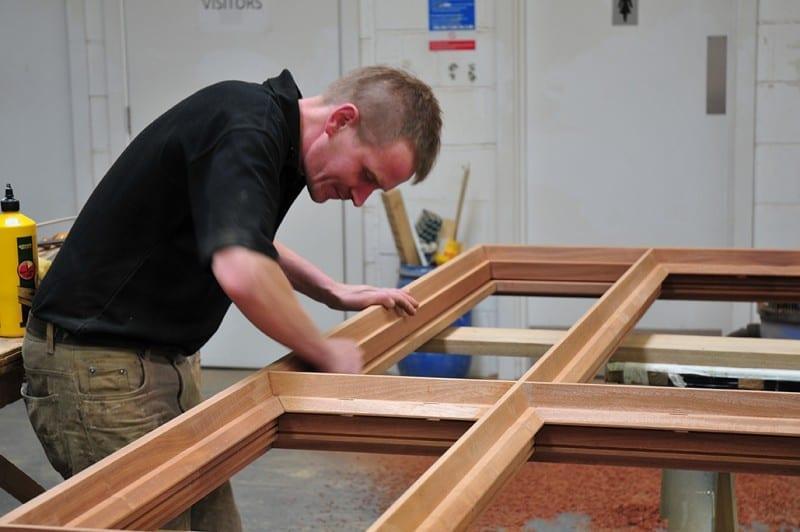 Worker making wooden window frames adding beading