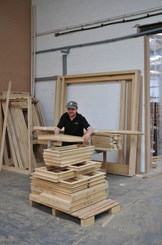 Worker with a pile of timber window frames ready for the next stage of the manufacture process