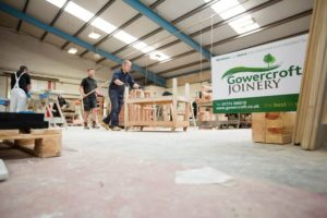 The Gowercroft Joinery wooden window manufacture plant with workers and a large sign