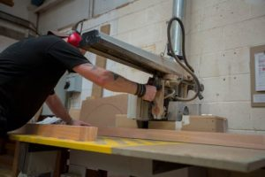 A worker operates an industrial buzz saw while making timber window frames