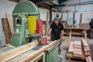 A worker with raw timber ready for manufacture of timber windows and doors