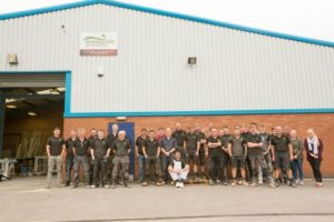 The staff line up for a photograph where they help make wooden windows and doors in the workshop