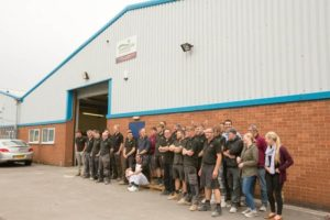 The staff line up for a photo outside the workshop where wooden windows are manufactured