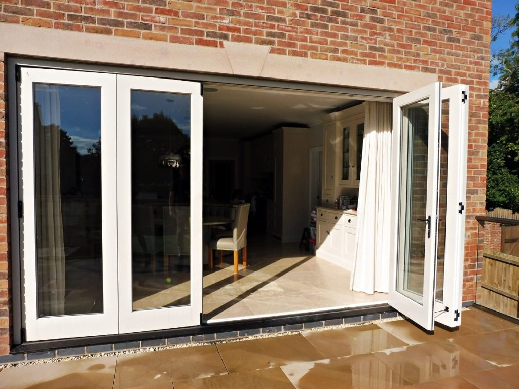 Tutbury bifold door 5 five panel painted strutt yellow clear glass partially open brick building stone lintel external view 2