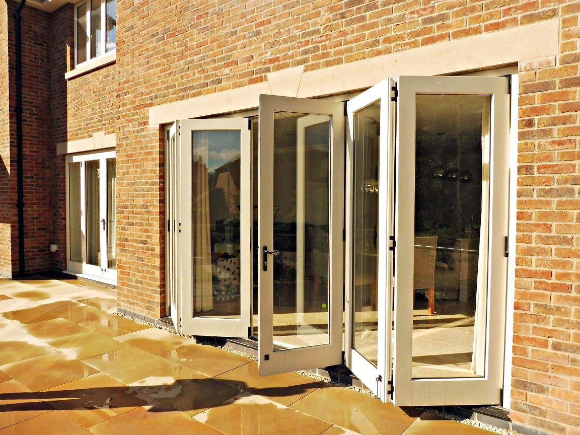 Tutbury bifold door 5 five panel painted strutt yellow clear glass partially open brick building stone lintel external view