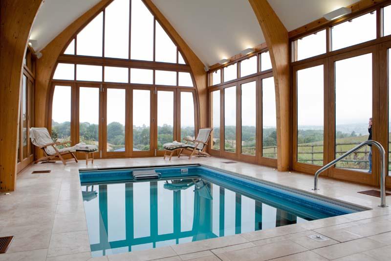 Tutbury sliding fold windows in Glulam structure swimming pool internal stained hardwood
