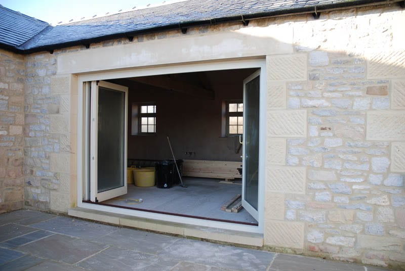 Main image of Halifax heritage bifold doors open in a barn conversion by gowercroft joinery
