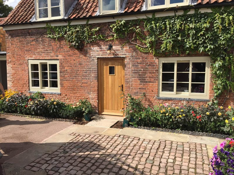 Horizontal sliding sash heritage windows and oak door in listed building restoration by Gowercroft Joinery