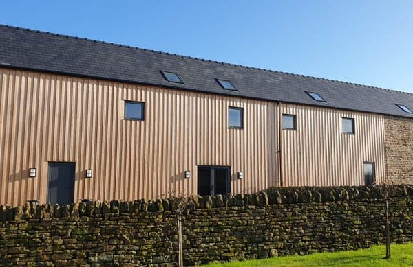 Rear view of Dunston Barn showing timber cladding and typical barn conversion square windows and roof lights