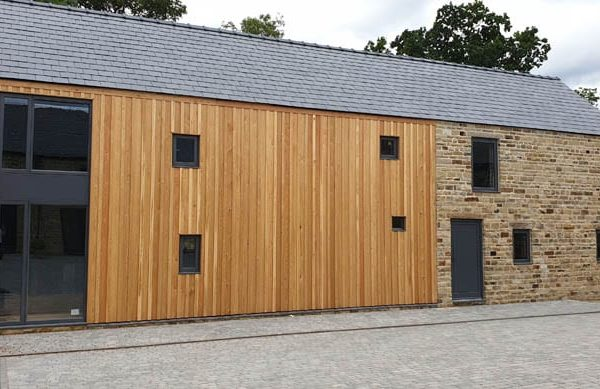 Low angle photo of the cladding to the rear of dunston barn with doors and timber windows for barn conversions