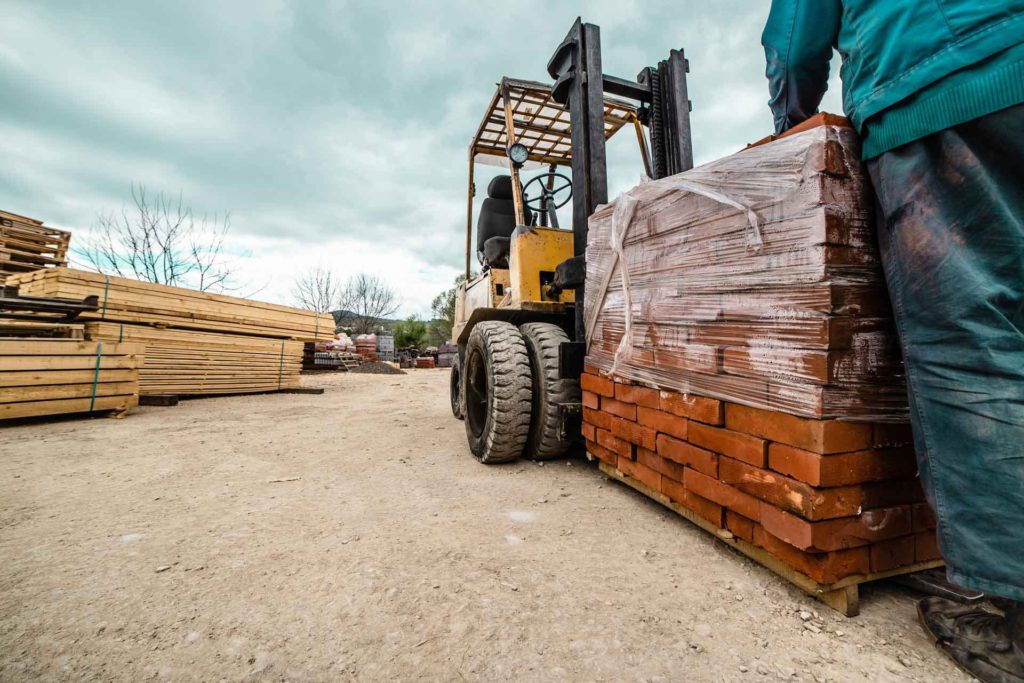 Who Sells Timber Windows? A fork truck delivering a pallet of bricks to a builders merchant where you can buy timber windows from