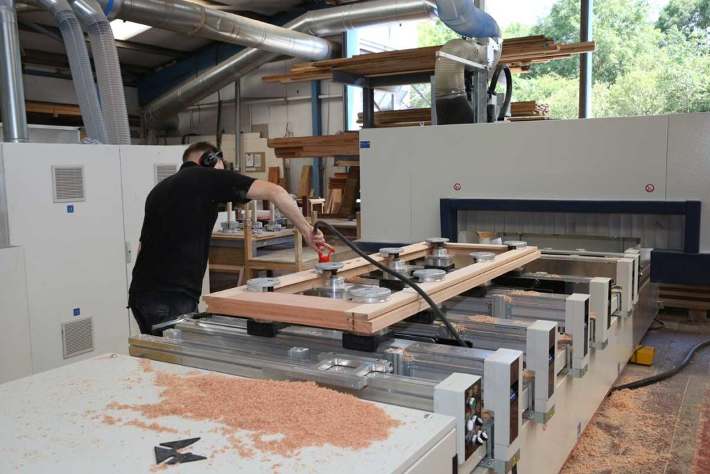 Who sells timber windows? A modern CNC router machine in a timber window manufacturers workshop where you can buy timber windows