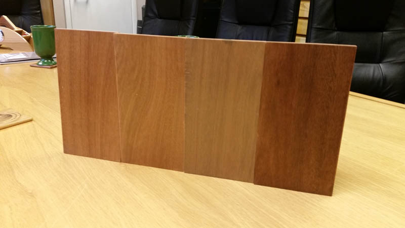 Red Grandis window frame stain samples on a table in the Gowercroft Office